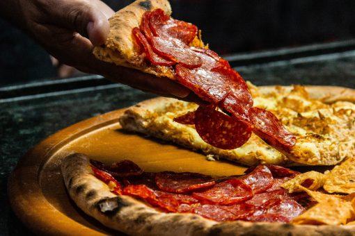 main de personne tenant une part de pizza au pepperoni en tranches
